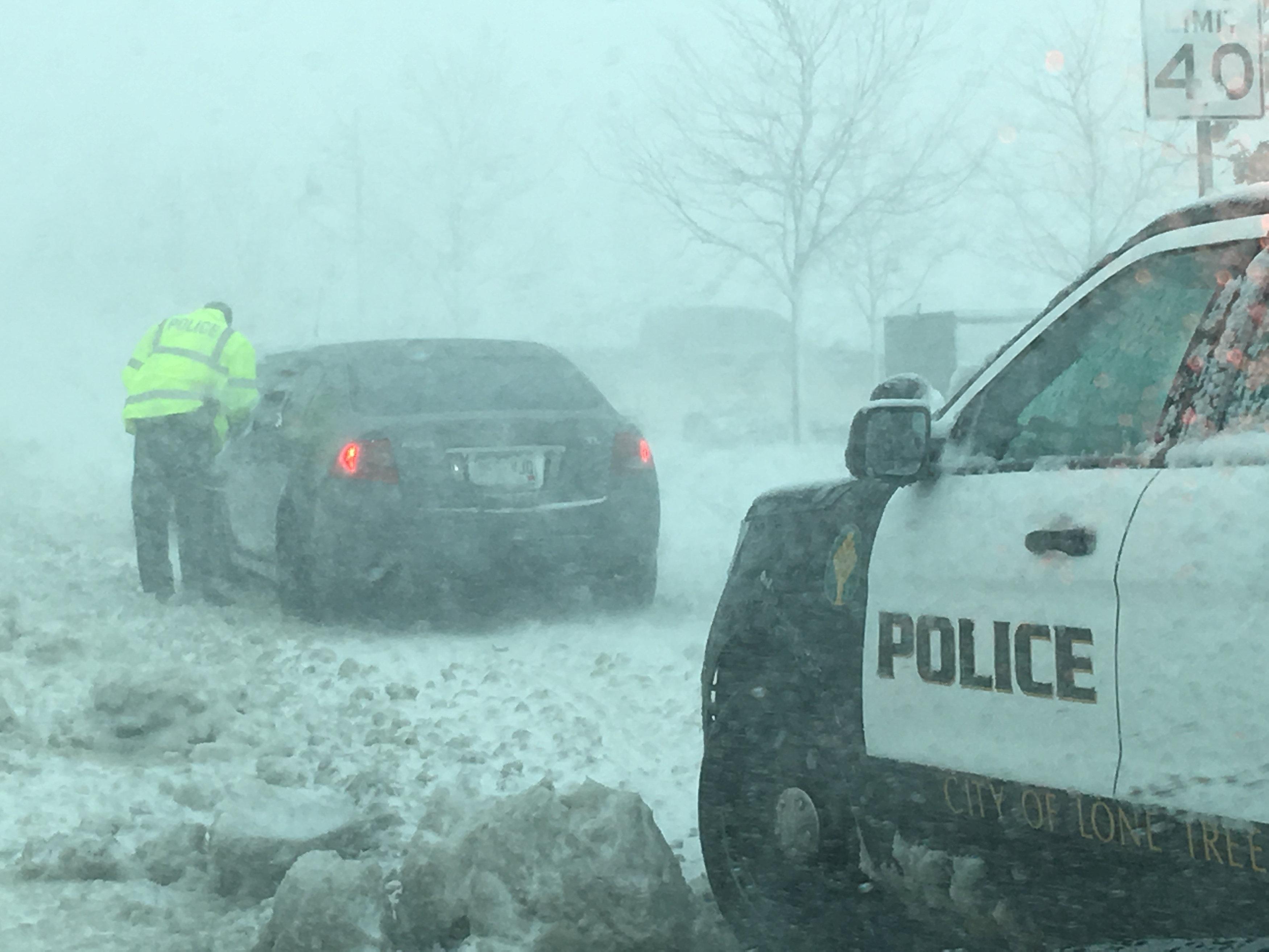 Un agente de la policía conversa con un conductor atascado en una vía de Lone Tree, Colorado.