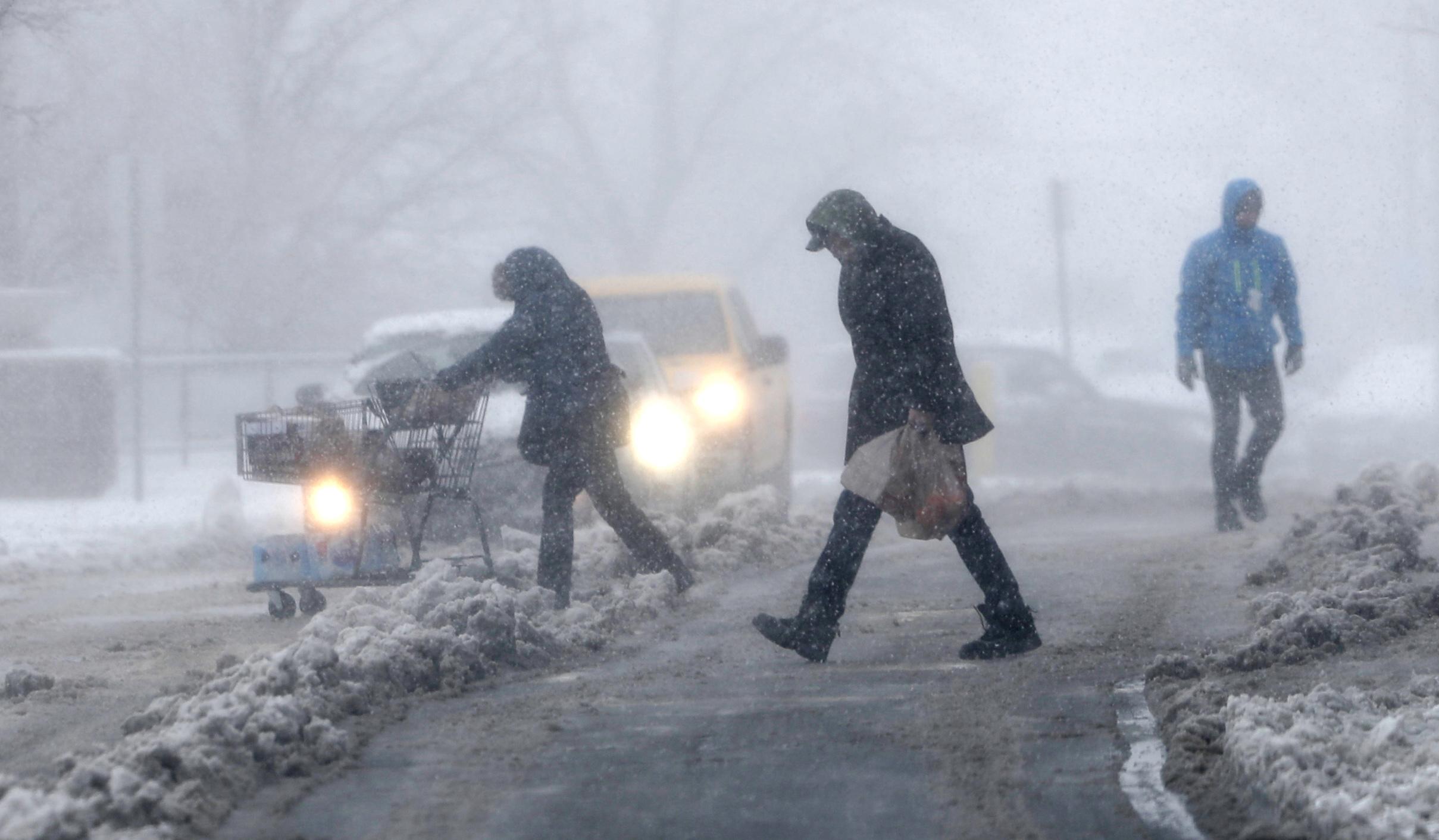Compradores luchan por regresar a los vehículos estacionados afuera de una tienda de comestibles mientras la tormenta de invierno azota Denver.