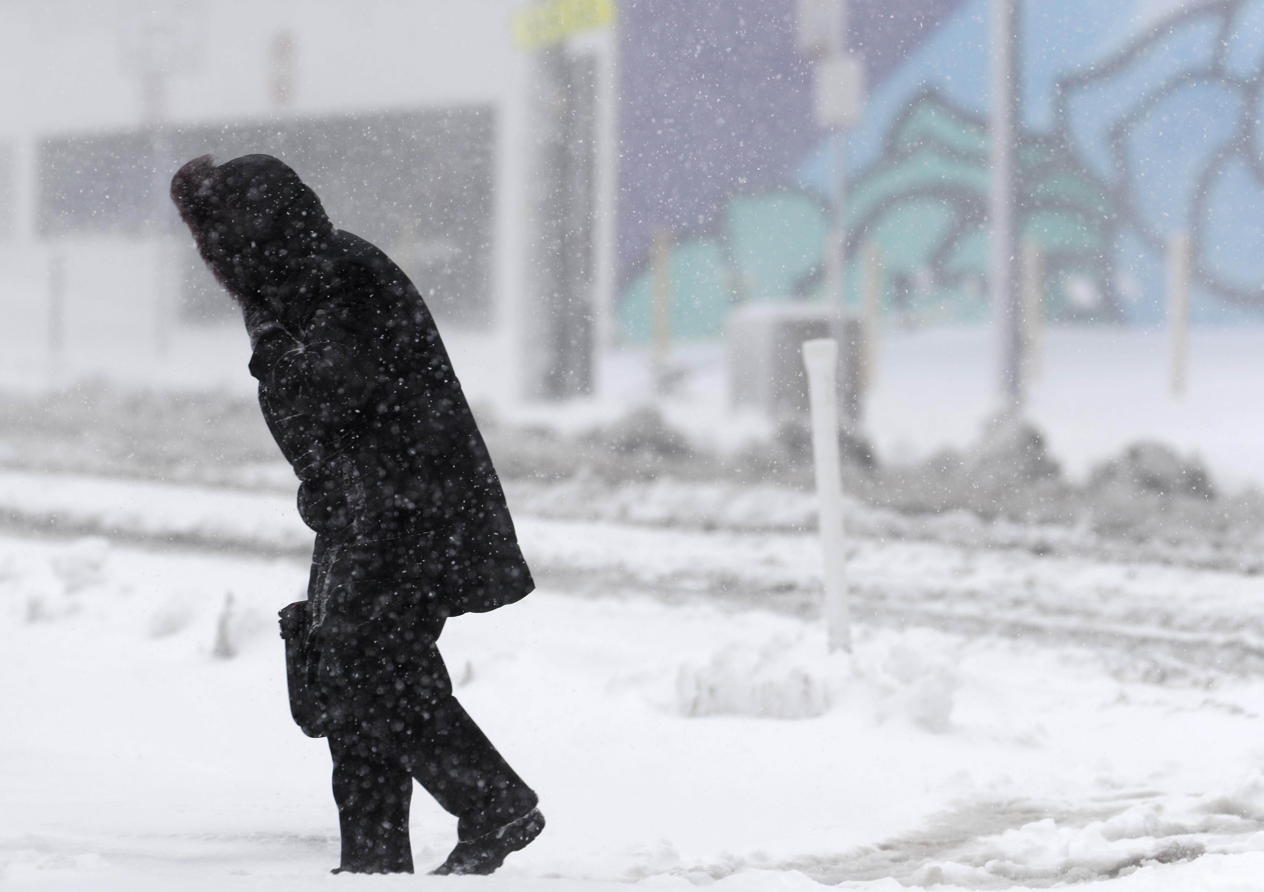 Un peatón solitario camina a lo largo de Broadway mientras la tormenta de finales de invierno arroja vientos huracanados y nieve en Denver.