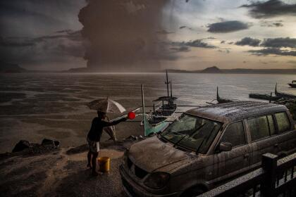 """TALISAY, PHILIPPINES - JANUARY 12: A resident splashes water on a vehicle covered in ash mixed with rainwater as Taal Volcano erupts on January 12, 2020 in Talisay, Batangas province, Philippines. Local authorities have begun evacuating residents near Taal Volcano as it began spewing ash up to a kilometer high Sunday afternoon. The Philippine Institute of of Volcanology and Seismology has raised the alert level to three out of five, warning of the volcano's continued """"magmatic unrest."""" (Photo by Ezra Acayan/Getty Images)"""