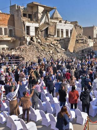 "People greet Pope Francis as he takes the podium at the square near the ruins of the Syriac Catholic Church of the Immaculate Conception (al-Tahira-l-Kubra), in the old city of Iraq's northern Mosul on March 7, 2021. - Pope Francis, on his historic Iraq tour, visits today Christian communities that endured the brutality of the Islamic State group until the jihadists' ""caliphate"" was defeated three years ago (Photo by Zaid AL-OBEIDI / AFP) (Photo by ZAID AL-OBEIDI/AFP via Getty Images)"