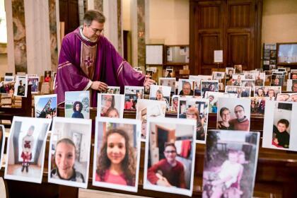 <b>Una misa sin fieles.</b> Giuseppe Corbari, párroco de una Iglesia en Giussano, en el norte de Italia, coloca en los asientos las fotografías de los que no pueden asistir a la misa por estar en cuarentena. 22 de marzo.