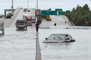 A man walks down the median as trucks navigate floodwaters from Tropical Storm Harvey along Interstate 610 Sunday, Aug. 27, 2017, in Houston, Texas. (AP Photo/David J. Phillip)