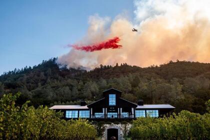 Un avión cisterna rocía retardante en una colina aleñada al viñedo Davis Estates en la ciudad de Calistoga. El edificio se salvó de ser calcinado por las llamas.