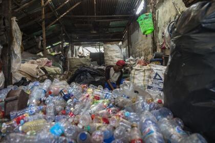 A garbage collector sorts plastic bottles in Surabaya on September 15, 2021. (Photo by Juni Kriswanto / AFP) (Photo by JUNI KRISWANTO/AFP via Getty Images)
