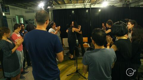 Refugees and immigrants come together to sing an improvised song with Eleni Arapoglou
