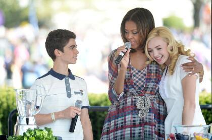 """En 2014, cuando trabajaba en  <b>la serie 'Jessie'</b>, tuvo la oportunidad de  <b>motivar a la juventud</b> en compañía de su colega, Peyton List (extrema derecha) y de la entonces primera dama de Estados Unidos Unidos,  <b><a href=""""https://www.univision.com/famosos/te-vas-a-reir-con-el-simpatico-chat-entre-michelle-obama-y-su-mama-sobre-la-aparicion-que-tuvo-en-los-grammy-fotos"""">Michelle Obama.</a></b>"""