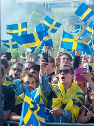 Stockholm, Sweden – July 1, 2015: Swedish football fans waving Swedish flags in Stockholm park Kungsträdgården. Thousands of Swedish football fans turned out to welcome back the Sweden players who won the country's first UEFA European Under-21 Football Championship title.