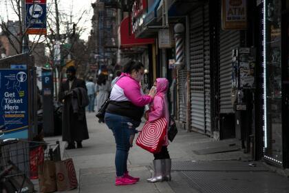<b>Precaución en las calles de Nueva York.</b> Una mujer le ajusta la máscara facial de un niño en una calle de East Village, el 19 de marzo. Estados Unidos es ahora el tercer país con más casos de coronavirus, después de China e Italia, y Nueva York es el estado más afectado.