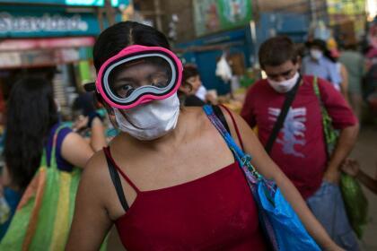 <b>Protección extrema. </b>Una mujer usa una máscara de buzo sobre la mascarilla de tela convencional para intentar protegerse del coronavirus, en Lima, Perú. 23 de marzo.