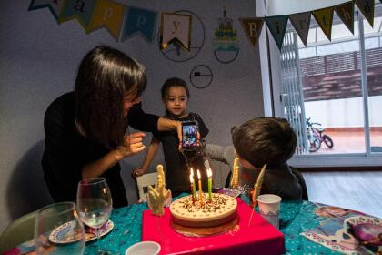 BARCELONA, SPAIN - APRIL 13: The photographer's wife, son and daughter, Elisenda Canari, Joel and Julia, show Julia's birthday cake to their grandparents via live-stream during her birthday party on April 13, 2020 in Barcelona, Spain. More than 17,000 people are reported to have died in Spain due to the COVID-19 outbreak, although the country has reported a decline in the daily number of deaths. (Photo by David Ramos/Getty Images)