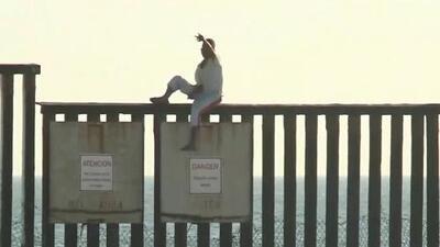 Migrantes de la caravana se trepan en la valla fronteriza entre Tijuana y San Diego