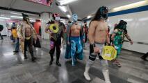 Luchadores reparten cubrebocas en el metro de México