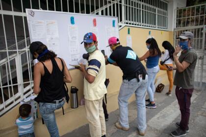 <b>Clases a distancia sin internet. </b>Un grupo de padres se reúne <b> </b>frente a una escuela en Caracas, Venezuela, para copiar las tareas de la semana que deben hacer sus hijos en casa. El país sudamericano tiene un servicio de Internet inestable y muy lento, y sólo una porción de la población puede realizar clases en línea. 27 de abril. <br>
