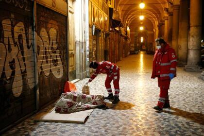 <b>Cuarentena en la calle.</b> Voluntarios de la Cruz Roja llevan alimentos y desinfectante a personas que duermen en las aceras aledañas a la plaza Vittorio, Roma, el 21 de marzo.
