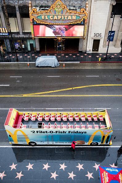 """Está visual aérea muestra a un autobús de turistas completamente vacío y la entrada el famoso teatro El Capitán, bloqueada. Todo por la medida del distanciamiento social, """"Más seguros en casa"""" que limita a las personas a salir solo por comida, medicinas y aquellos empleos esenciales. <br>"""