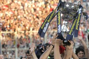 Buenos Aires, ARGENTINA: Estudiantes' team captain Juan Veron (C) holds the trophy between striker Mariano Pavone (L) and other players at the end of the final match of the Argentine Apertura soccer tournement against Boca Juniors at Jose Amalfitani stadium in Buenos Aires, 13 December 2006. Estudiantes won 2-1 and became the champion. AFP PHOTO/JUAN MABROMATA (Photo credit should read JUAN MABROMATA/AFP/Getty Images)