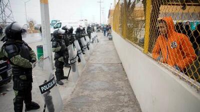 Migrantes intentan salir a la fuerza del albergue de Piedras Negras, en México, donde permanecen aislados