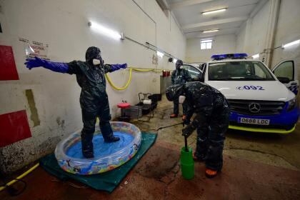<b>Desinfección total en España.</b> Voluntarios de un equipo de rescate limpian los trajes y vehículos que llevaron para atender enfermos de covid-19, en Pamplona, en el norte del país.