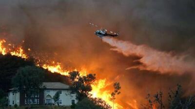 """""""Quise proteger mi casa"""": vecinos desafían el fuego que ya quemó 18,000 acres en el sur de California"""