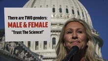 Marjorie Taylor Greene cuelga un letrero anti-transgénero frente a la oficina de una legisladora que tiene una hija trans