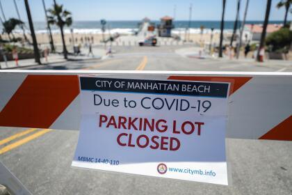 """""""Estacionamiento cerrado por covid-19"""", se lee en los anuncios de la ciudad de Manhattan Beach que limita el paso a la zona cerca del mar."""