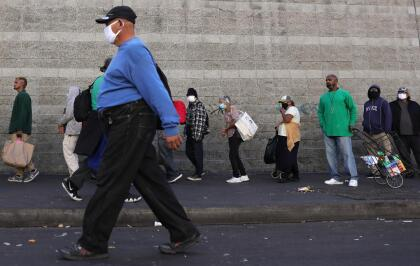 LOS ANGELES, CALIFORNIA - DECEMBER 25: A pedestrian walks past as community members wait in line to receive holiday-themed takeout meals and backpacks with toiletries from the Midnight Mission in Skid Row on Christmas day amid the COVID-19 pandemic on December 25, 2020 in Los Angeles, California. California has become the first state to hit 2 million COVID-19 cases. Southern California remains at zero percent of its available ICU (Intensive Care Unit) bed capacity amid a spike in coronavirus cases and hospitalizations. (Photo by Mario Tama/Getty Images)