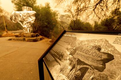 Fire-resistant wrap covers a historic welcome sign as the KNP Complex Fire burns in Sequoia National Park, Calif., on Wednesday, Sept. 15, 2021. The blaze is burning near the Giant Forest, home to more than 2,000 giant sequoias. (AP Photo/Noah Berger)