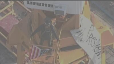 Un hombre sube a la grúa de una construcción en Miami con lo que parece ser un mensaje para Trump