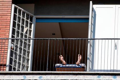<b>Tomando el Sol.</b> Un residente de Roma recibe los rayos del Sol en la ventana mientras sigue las recomendaciones de las autoridades de no salir de casa, el 21 de marzo. Italia ya casi duplicó la cantidad de fallecidos por covid-19 que tuvo China, donde se originó el brote.