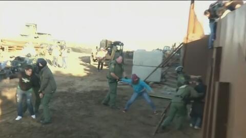 El dramático momento en que una familia hondureña salta la valla de Tijuana con un bebé en brazos
