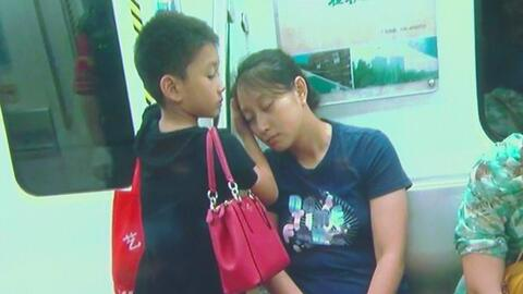 Un niño chino da ejemplo de ternura y compasión cuidando el sueño de su madre cansada en el metro