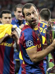 Barcelona's Javier Mascherano celebrates with the trophy after winning the Champions League final soccer match against Manchester United at Wembley Stadium, London, Saturday, May 28, 2011. (AP Photo/Jon Super)