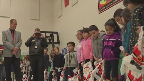 En compañía de Santa Claus, policía estatal de Illinois entrega regalos a niños de una escuela