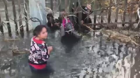 Revelan dramáticas imágenes de migrantes cruzando con niños a través de alambres de púas en la frontera