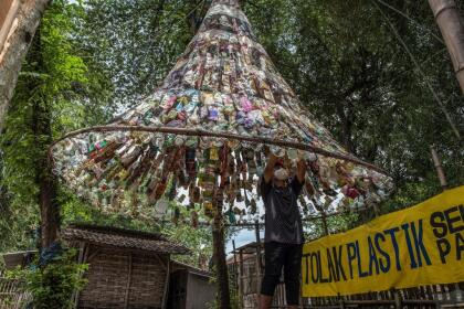 An Indonesian activist from ECOTON (ecological observation and wetland conservation) prepares an installation made with used plastic, including 4,444 bottles, collected from the river in Gresik on September 17, 2021, to raise public awareness of plastic waste in rivers and oceans. (Photo by JUNI KRISWANTO / AFP) (Photo by JUNI KRISWANTO/AFP via Getty Images)