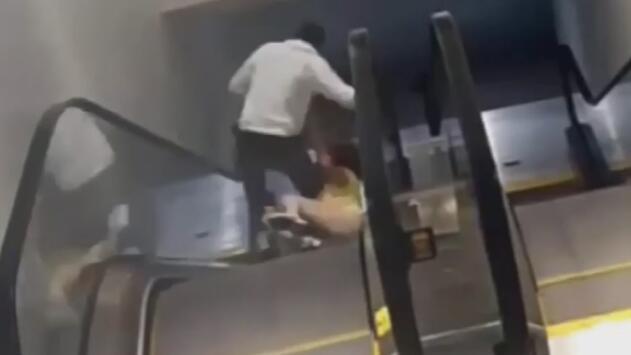 Una mujer rueda por una escalera eléctrica al ser asaltada por un hombre en un centro comercial
