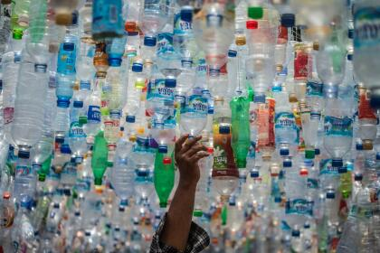 TOPSHOT - An Indonesian activist from ECOTON (ecological observation and wetland conservation) prepares an installation made with used plastic, including 4,444 bottles, collected from the river in Gresik on September 17, 2021, to raise public awareness of plastic waste in rivers and oceans. (Photo by JUNI KRISWANTO / AFP) (Photo by JUNI KRISWANTO/AFP via Getty Images)