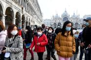 TOPSHOT - Tourists wearing protective facemasks visit the Piazza San Marco, in Venice, on February 24, 2020 during the usual period of the Carnival festivities which the last two days have been cancelled due to an outbreak of the COVID-19 the novel coronavirus, in northern Italy. - Italy reported on February 24, 2020 its fourth death from the new coronavirus, an 84-year old man in the northern Lombardy region, as the number of people contracting the virus continued to mount. (Photo by ANDREA PATTARO / AFP) (Photo by ANDREA PATTARO/AFP via Getty Images)