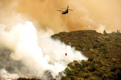 A helicopter battles the KNP Complex Fire burning along Generals Highway in Sequoia National Park, Calif., on Wednesday, Sept. 15, 2021. The blaze is burning near the Giant Forest, home to more than 2,000 giant sequoias. (AP Photo/Noah Berger)
