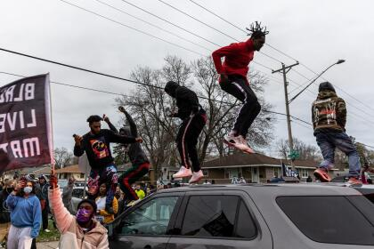 Protesters stand on top of a police car as they clash after an officer shot and killed a black man in Brooklyn Center, Minneapolis, Minnesota on April 11,2021. - Protests broke out April 11, 2021 night after US police fatally shot a young Black man in a suburb of Minneapolis -- where a former police officer is currently on trial for the murder of George Floyd. Hundreds of people gathered outside the police station in Brooklyn Center, northwest of Minneapolis. Police fired teargas and flash bangs at the demonstrators, according to an AFP videojournalist at the scene. (Photo by Kerem Yucel / AFP) (Photo by KEREM YUCEL/AFP via Getty Images)
