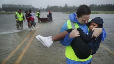 Este reportero 'lucha' en vivo contra el viento de Florence... mientras dos peatones andan tan campantes