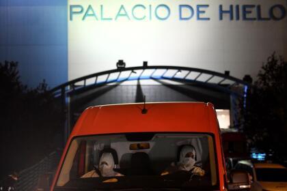 <b>La peor cara de la pandemia. </b>Miembros de la Unidad de Emergencia del Ejército de España llegan al centro comercial Palacio de Hielo, de Madrid, donde una pista de patinaje sobre hielo será convertida en una morgue temporalmente, el 23 de marzo. En ese país más de 500 personas murieron en las últimas 24 horas.