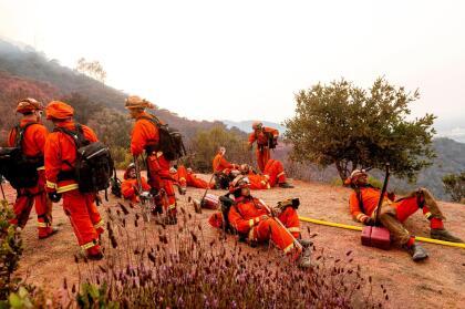 Bomberos toman un descanso luego de luchar a marchas forzadas contra el incendio River en el condado de Salinas.