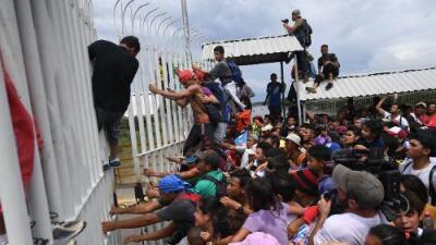 Caravana de migrantes cruza masivamente la frontera de Guatemala rumbo a México rompiendo la cerca del control fronterizo
