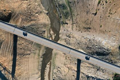 OROVILLE, CALIFORNIA - JULY 22: In an aerial view, the Enterprise Bridge crosses over a section of Lake Oroville that was previously underwater on July 22, 2021 in Oroville, California. As the extreme drought emergency continues in California, Lake Oroville's water levels are continuing to drop to 28 percent of capacity. State water officials say that Lake Oroville's Edward Hyatt Powerplant might be forced to shut down the hydroelectric plant as soon as August or September if water levels continue to drop. (Photo by Justin Sullivan/Getty Images)