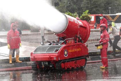 <b>Desinfectante a chorros. </b> Bomberos rocían masivamente líquido para matar el coronavirus en Yakarta, Indonesia, el domingo 22 de marzo.
