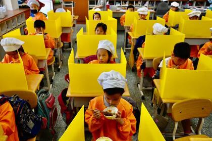 <b>Escritorios con barreras.</b> Los estudiantes de una escuela primaria en Taipei, Taiwan, tomando su almuerzo en el aula el 29 de abril. Allí los escritorios fueron separados con paneles de plástico para mantener la distancia entre los niños. En varios países las escuelas han reabierto, pero existen nuevos procedimientos y precauciones a seguir.