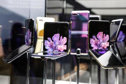 Los diferentes modelos del Galaxy Z Flip expuestos al público de la feria Unpacked 2020. Motorola también ha entrado a la competencia de los celulares de pantalla plegable con su nuevo Razr, a un precio de 1,500 dólares. <br>