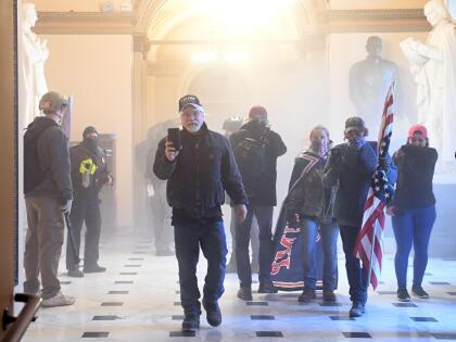 Supporters of US President Donald Trump enter the US Capitol as tear gas fills the corridor on January 6, 2021, in Washington, DC. - Demonstrators breeched security and entered the Capitol as Congress debated the a 2020 presidential election Electoral Vote Certification. (Photo by Saul LOEB / AFP) (Photo by SAUL LOEB/AFP via Getty Images)